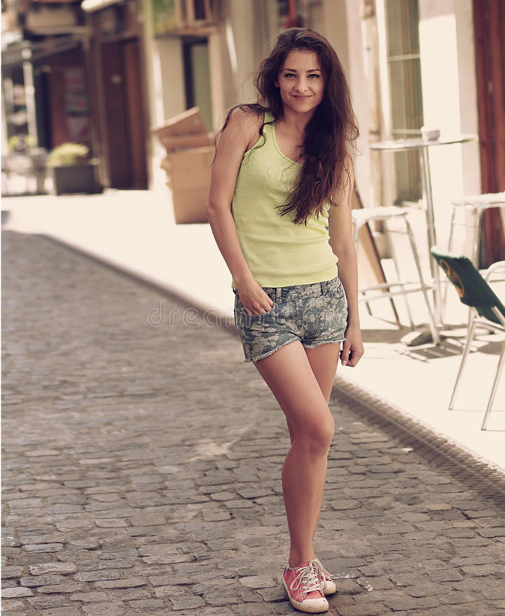 Beautiful long hair woman walking in old european town in short stock photography