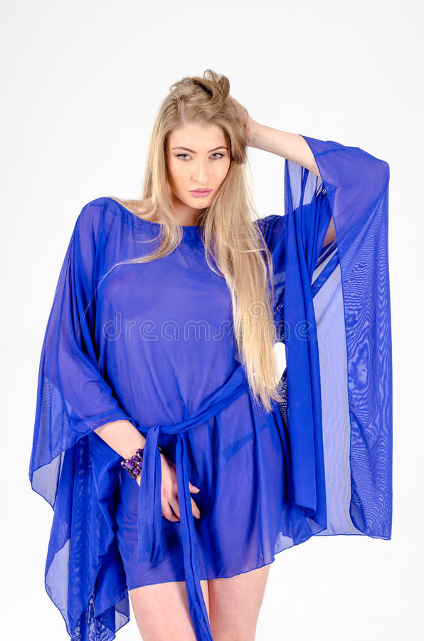 Beautiful long-haired blonde in a clear blue tunic and blue shoes. Fun stock photography