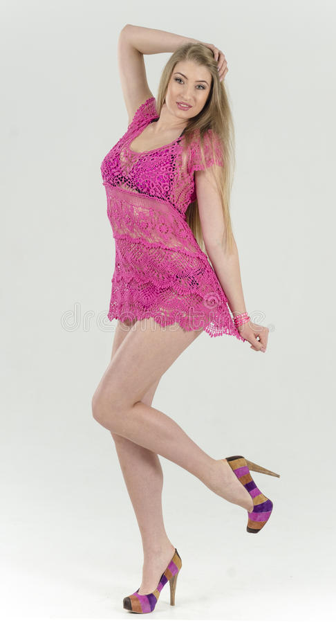 Beautiful long-haired blonde in a pink dress standing lush, flirty skirt lifting royalty free stock images