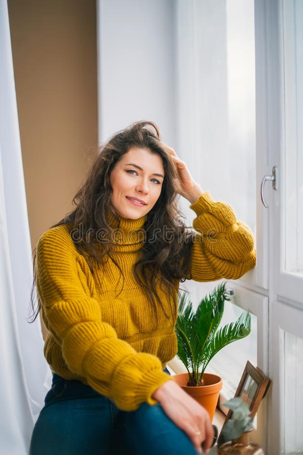 Beautiful long-haired girl, sitting on a window-sill stock photography