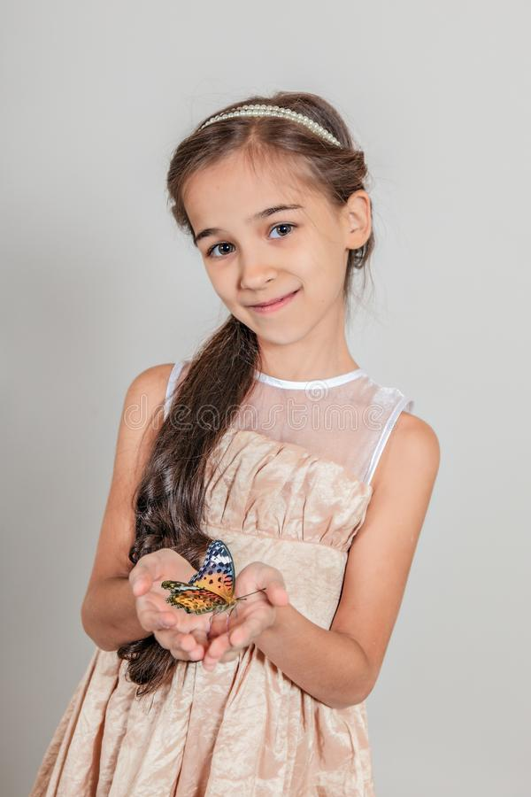 Beautiful long-haired girl smiling . The child is holding a butterfly on isolated grey background. royalty free stock photo