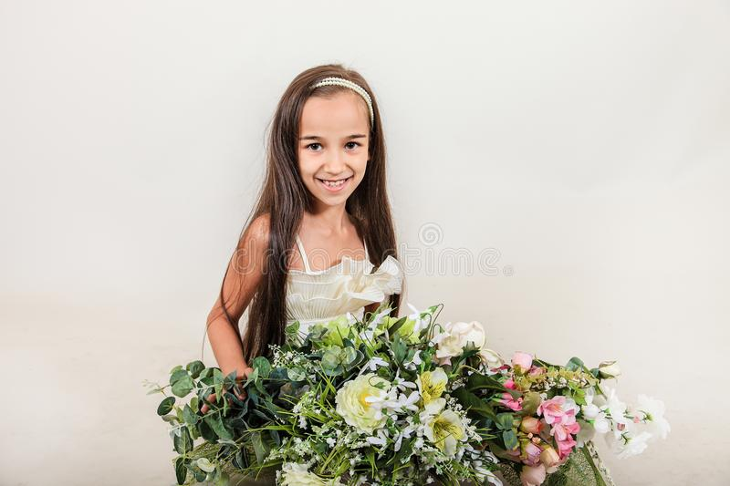 Beautiful long-haired girl smiling . on her face there is delight and surprise. The child holds a huge bouquet of flowers on isola stock photography