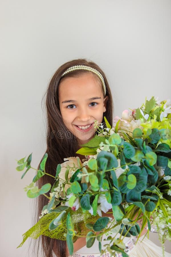 Beautiful long-haired girl smiling . on her face there is delight and surprise. The child holds a huge bouquet of flowers on isola stock photos