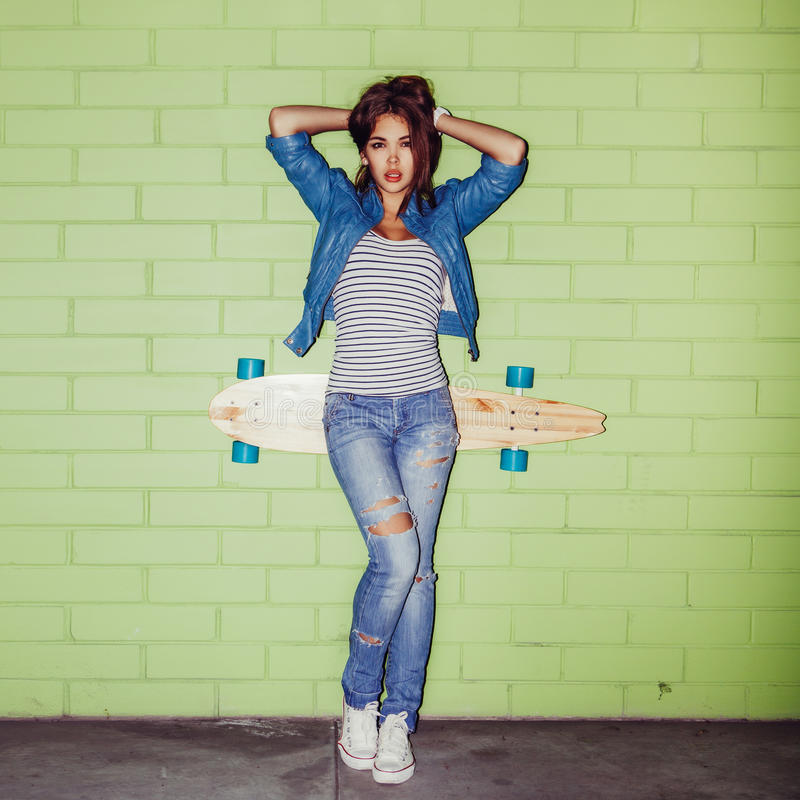 Beautiful long-haired girl with a wooden longboard near a green stock photos