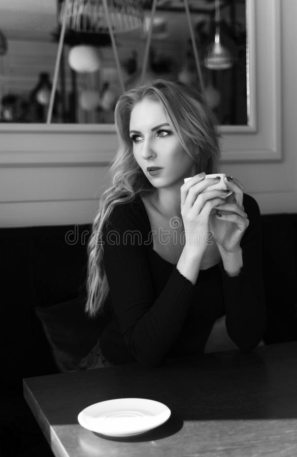 A beautiful long-haired, leggy blonde girl wearing a mini skirt sits and rests at a table, holds a cup of coffee in a cafe and stock photo