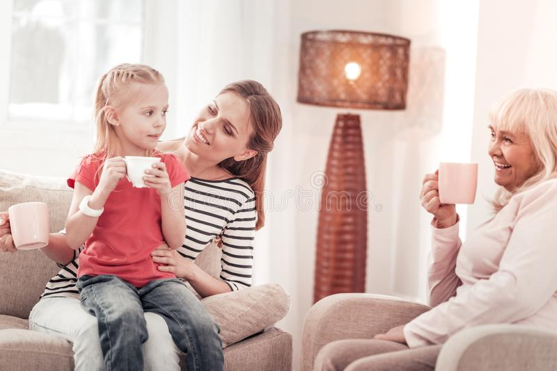 Beautiful long-haired mother feeling gorgeous with her daughter royalty free stock image