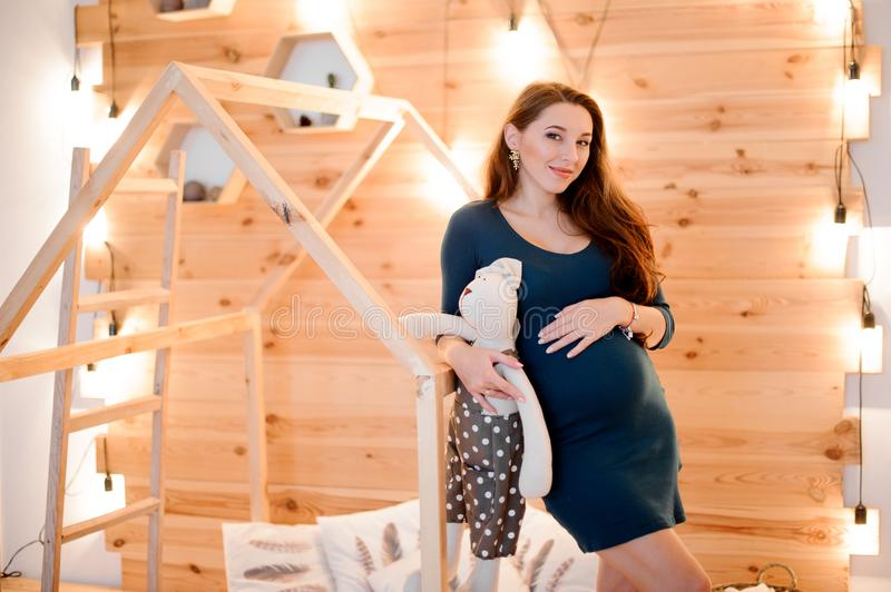 Beautiful long-haired pregnant woman with a toy among the lights of garlands stock image