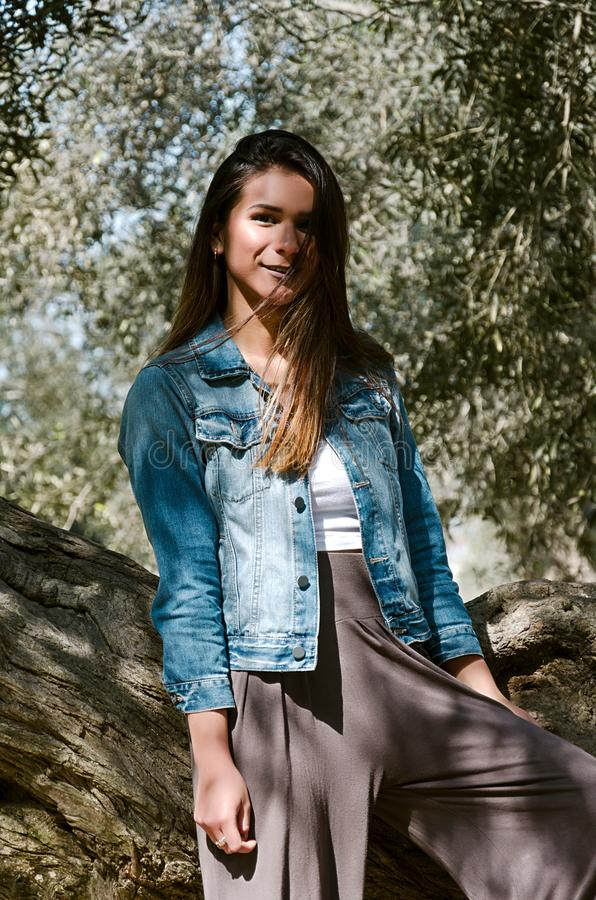 Beautiful long-haired teen woman with brown hair leaning on a tree royalty free stock photography