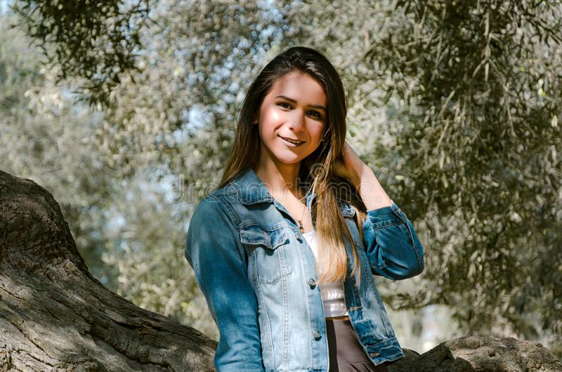 Beautiful long-haired teen woman with brown hair leaning on a tree. In the park stock photo