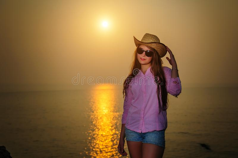 Beautiful long-haired woman against sunset on the sea. Young girl in sunglasses holding a hat and standing by the water. Warm royalty free stock photos