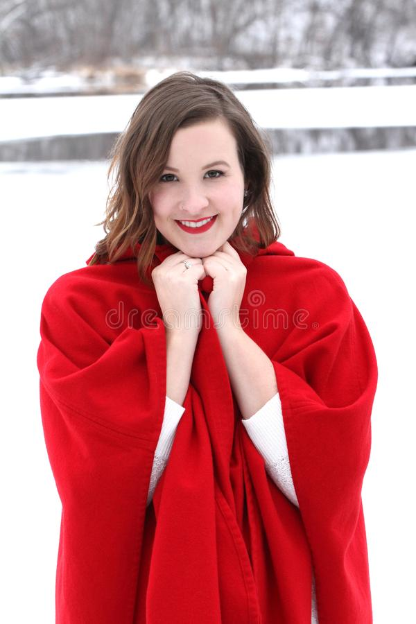 Beautiful long haired woman in vintage red cape riverside in winter stock photography