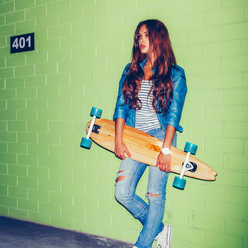 Beautiful long-haired woman with a wooden long skateboard near a royalty free stock image