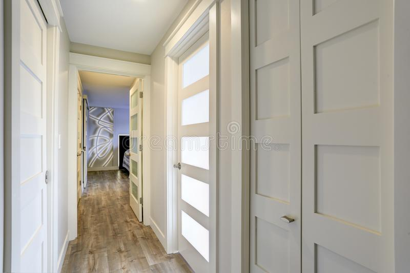 Long, narrow corridor with white doors accented with glass panels stock photography