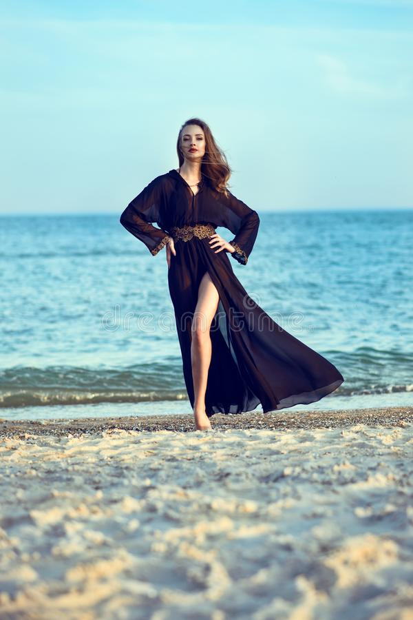 Beautiful long legged woman wearing trendy chiffon oriental black chiffon beach cover up stepping lightly on the sand royalty free stock photo