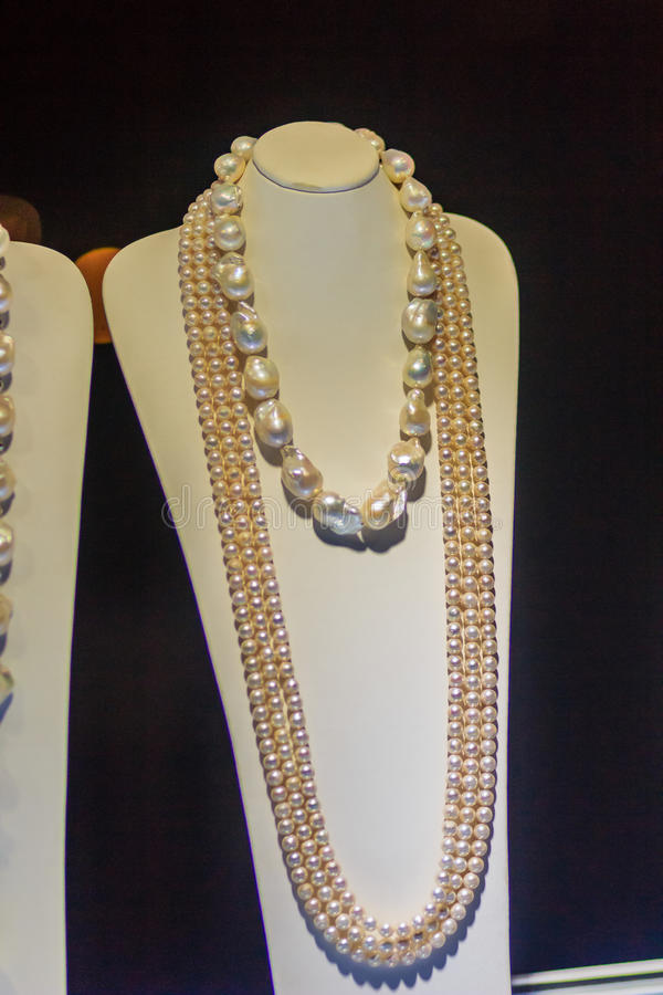 Beautiful long pearl necklaces are displayed at a jewelry shop. Poor light with noise grain shot stock images