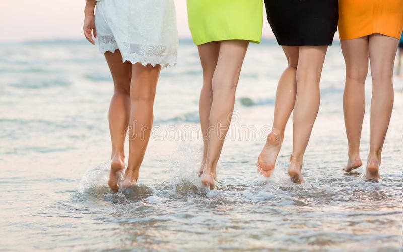 Beautiful, long and smooth women`s legs walk on the sand near the sea. Girls on the summer beach. Beautiful legs of girls. royalty free stock photo