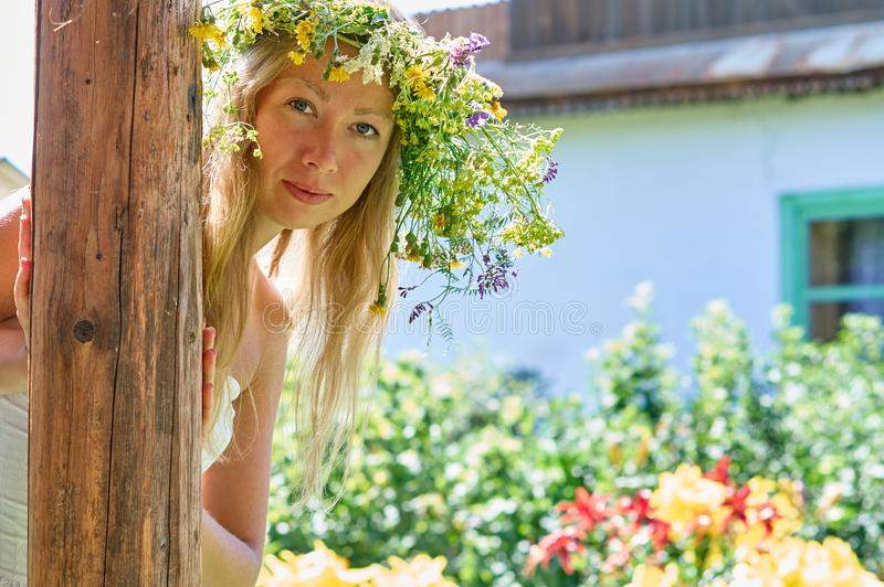 Beautiful long-white hair woman in white dress and flower wreath peeking playfully from behind a wooden pillar on yard of your. Beautiful long-white hair woman stock image