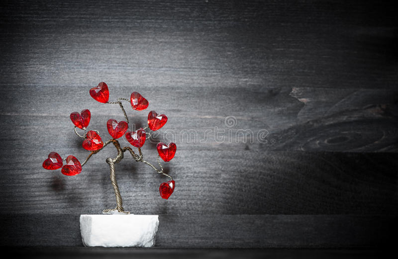 Beautiful love tree with red hearts on it. Beautiful love tree with red hearts on wooden background royalty free stock photography