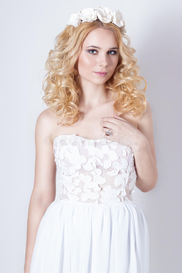 Beautiful lovely gentle elegant young blond woman in a white sundress chiffon and curls, and a wreath of flowers in her hair stock images