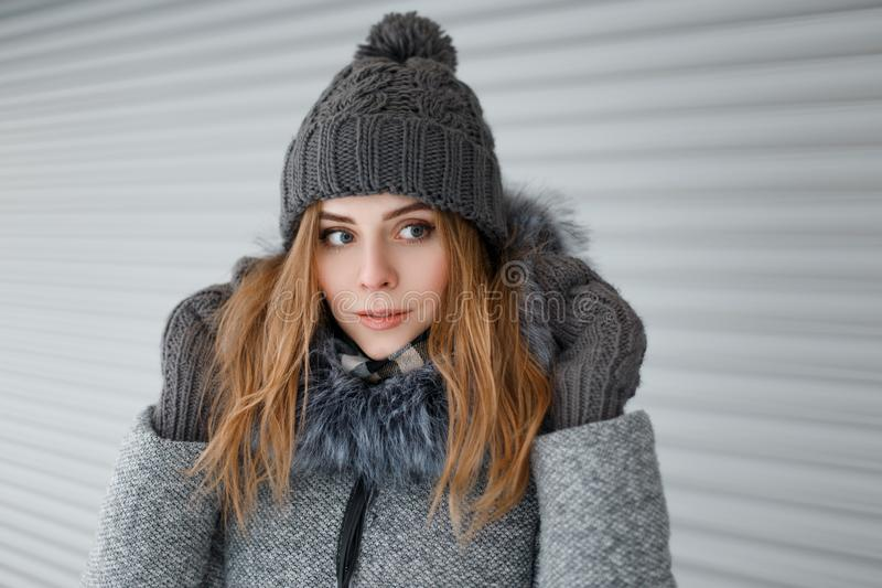 Beautiful lovely young woman with blue eyes in a knitted hat in a gray winter coat with fur in vintage warm mittens. Near a white metal wall. Beautiful girl on royalty free stock photos