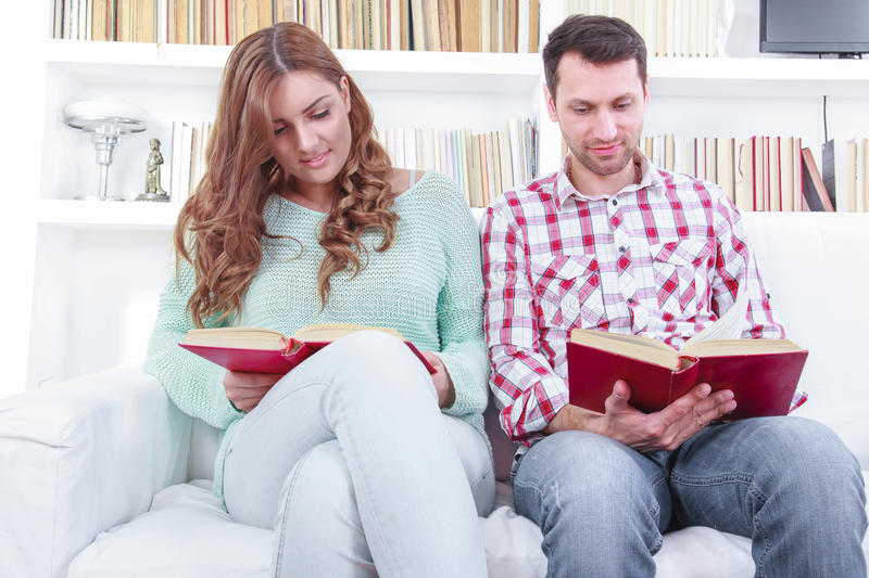 Beautiful loving casual couple reading a book on the sofa. Domestic atmosphere with library background stock photo