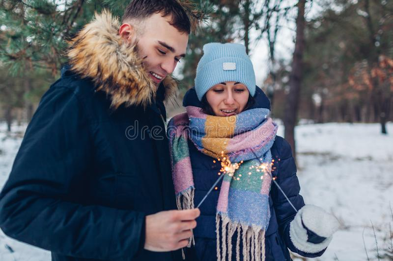Beautiful loving couple burning sparklers in winter forest. Christmas and New year concept stock image