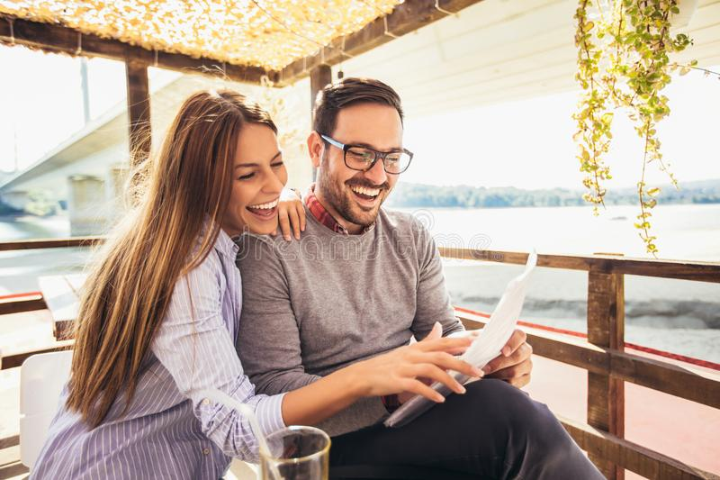 Beautiful loving couple sitting in a cafe enjoying in coffee stock photography