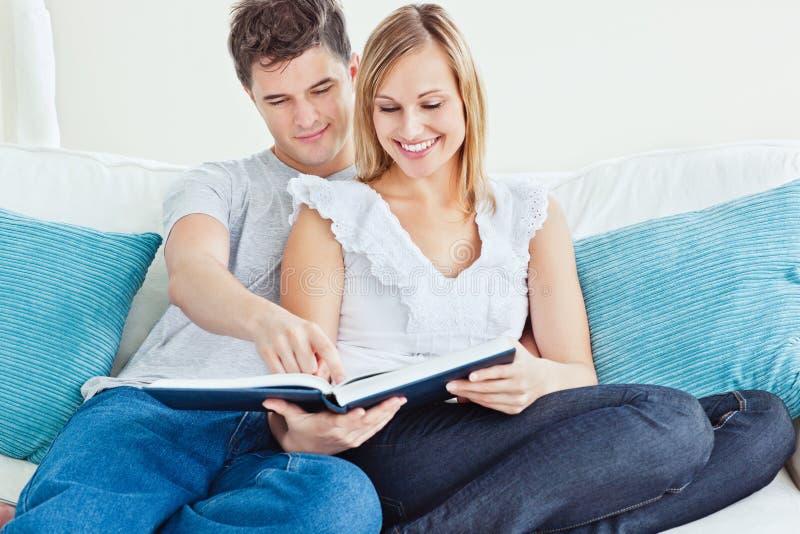 Beautiful loving couple watching photo album royalty free stock image