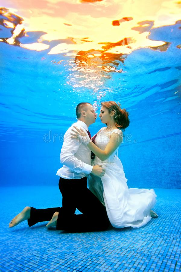 Beautiful loving couple in wedding dresses stands on her knees underwater at the bottom of the pool. royalty free stock photos