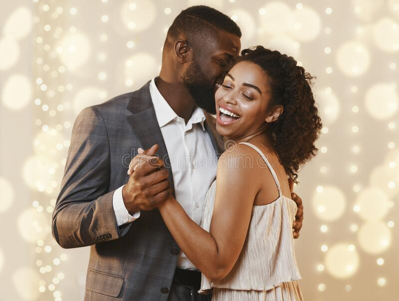 Beautiful happy black couple dancing in modern restaurant. Beautiful loving happy afro couple dancing in modern restaurant. Celebrating St Valentine`s Day stock images