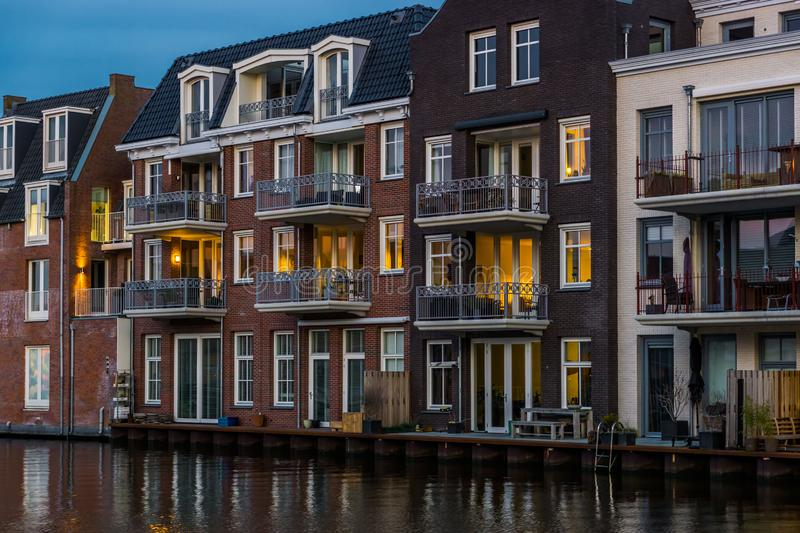 Beautiful and luxurious terraced houses at the canal, Dutch city architecture by night, Alphen aan den Rijn, The Netherlands. A beautiful and luxurious terraced royalty free stock photo