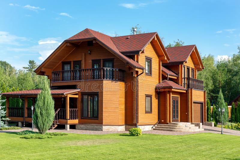 Beautiful luxury big wooden house. Timber cottage villa with with green lawn, garden and blue sky on background.  royalty free stock images