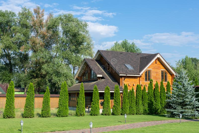 Beautiful luxury big wooden house. Timber cottage villa with with green lawn, garden and blue sky on background.  stock image