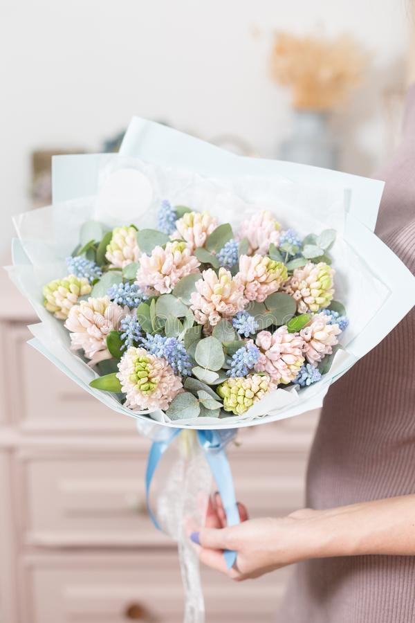Beautiful luxury bouquet of pink hyacinths flowers in woman hand. the work of the florist at a flower shop. stock photos