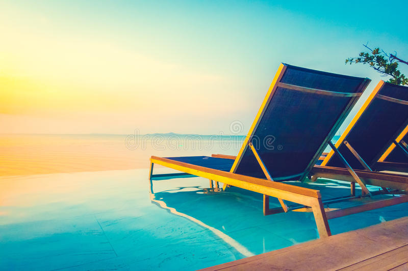 Beautiful luxury hotel swimming pool resort. With umbrella and chair on the beach and sea - Vintage Filter and Boost up color Processing stock photography