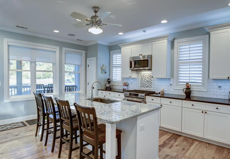 Beautiful luxury kitchen with quarz countertops and view windows stock photo