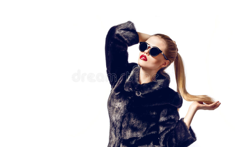 Beautiful luxury model with red lips and blonde hair in black fur coat royalty free stock photography
