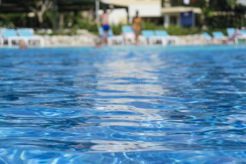 Beautiful luxury swimming pool in hotel resort with silhouette man and women. Around pool with sunshine and water reflection royalty free stock photo