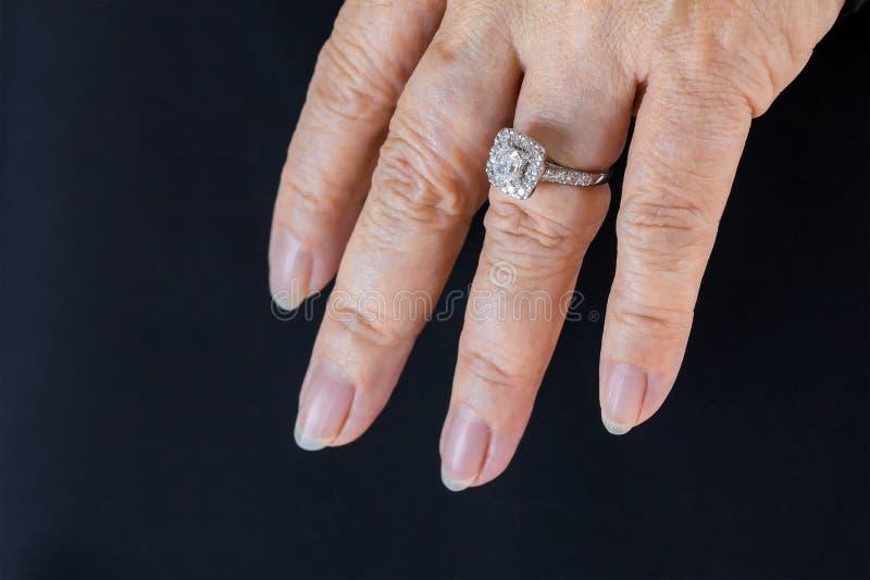 Beautiful and luxury wedding diamond ring worn on woman hand on black fabric background royalty free stock photography
