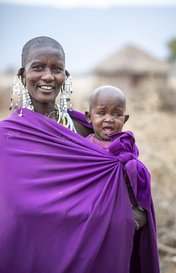 Beautiful maasai woman with a kid stock photo