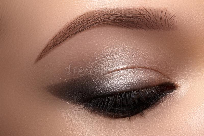 Beautiful Macro Eyes with Smoky Cat Eye Makeup. Cosmetics and Make-up. Closeup of Fashion Visage with Liner, Eyeshadows royalty free stock photography