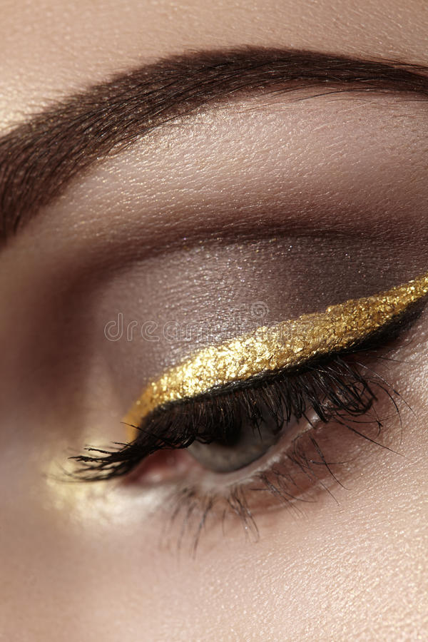 Beautiful macro shot of female eye with ceremonial makeup. Perfect shape of eyebrows, eyeliner and pretty gold line on eyelid royalty free stock photos