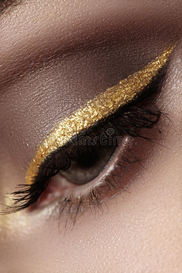 Beautiful macro shot of female eye with ceremonial makeup. Perfect shape of eyebrows, eyeliner and pretty gold line on eyelid. Cosmetics and make-up. Closeup royalty free stock images