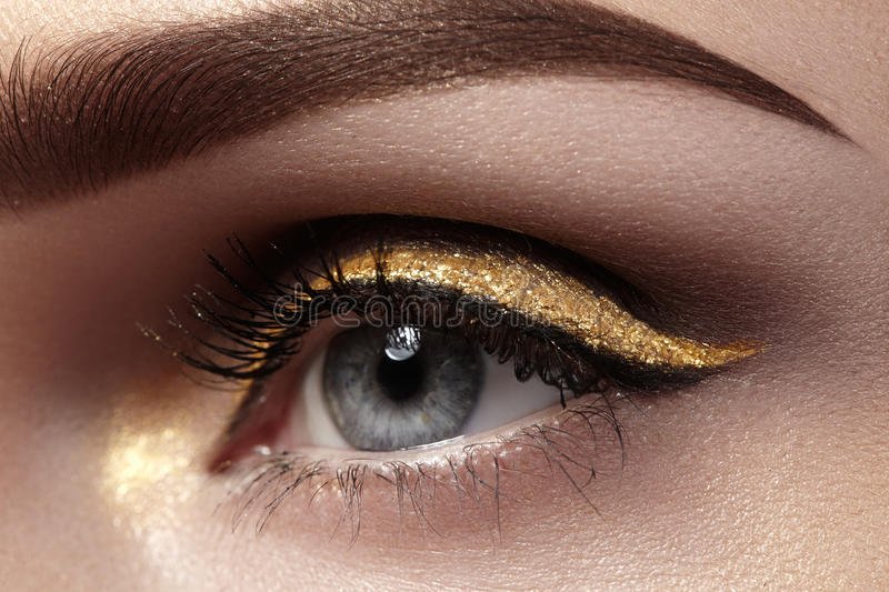 Beautiful macro shot of female eye with ceremonial makeup. Perfect shape of eyebrows, eyeliner and pretty gold line on eyelid stock images