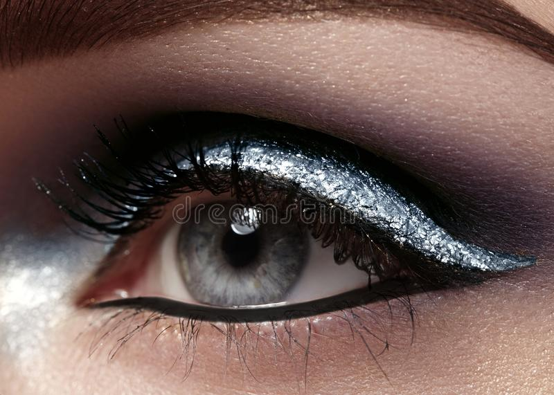 Beautiful macro shot of female eye with ceremonial makeup. Perfect shape of eyebrows, eyeliner and silver line on eyelid royalty free stock images