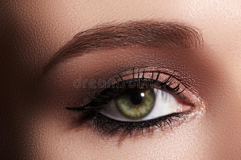 Beautiful Macro Shot of Female Eye with Classic Eyeliner Makeup. Perfect shape of eyebrows. Cosmetics and make-up stock photos