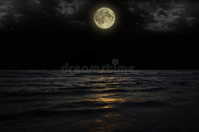Beautiful magic blue night sky with clouds and full moon stars reflexion in water.  royalty free stock images