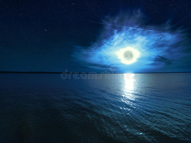 Beautiful magic blue night starry sky with clouds and full moon with reflexion of moonlight in the water royalty free stock photos