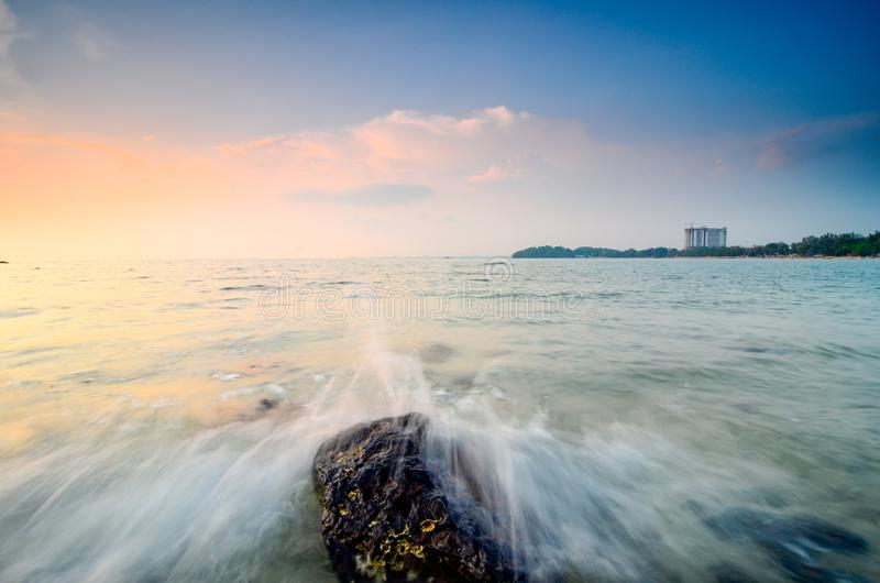 Beautiful and magical sunrise moment near the sea shore with cloudy sky. Soft wave hitting the sandy beach stock photo