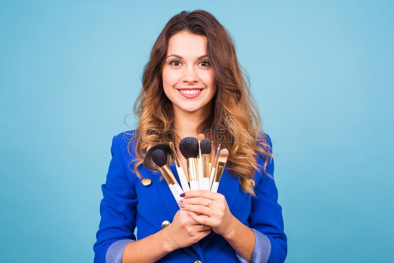 Beautiful make-up artist with brushes on blue background stock images